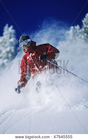 Skier skiing in powder snow against clear sky