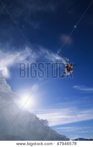 Low angle view of skier performing somersault against sky