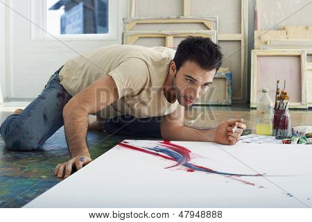Young male artist looking at canvas on studio floor
