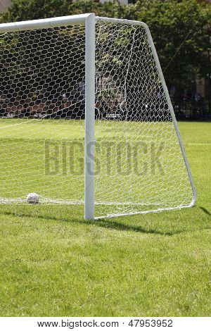 A shot of a soccer goal at the end of a empty field at a park