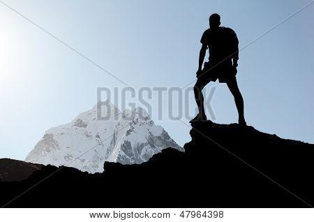 Man hiking silhouette in Himalaya mountains.