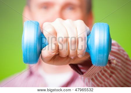 Hand with blue dumbell. Man in shirt as a concept of healthy office living.