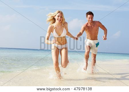 Couple Running Through Waves On Beach Holiday