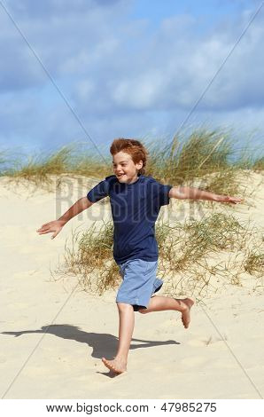Full length of a young boy running down sand dune on beach