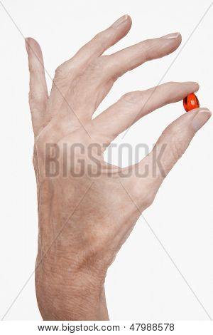 Closeup of a woman holding red pill between finger and thumb against white background