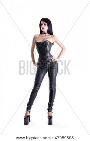 Sexy goth girl in leather corset and pants, isolated on white background