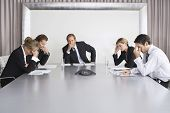 Group of serious business people on conference call in boardroom poster