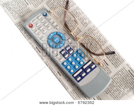 Newspaper, spectacles and board of the remote control