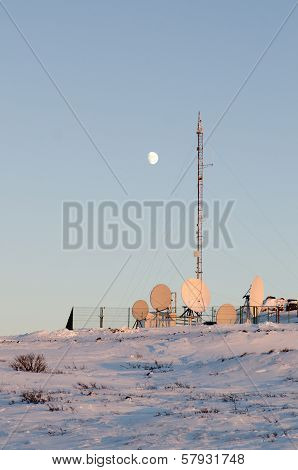 Moon Above Arctic Cell Site Illuminated By The Setting Sun