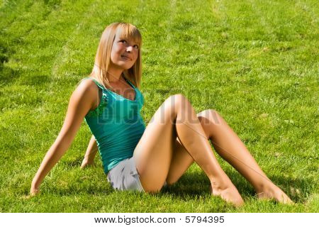 Young Smiling Girl Sitting On The Grass