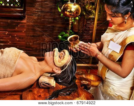 Woman having facial oil eyes mask at ayurveda spa.