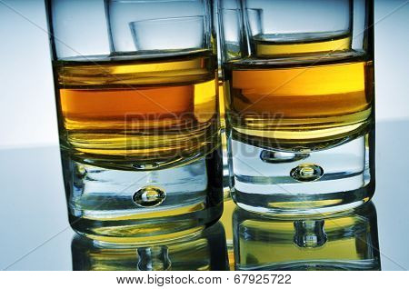 closeup of some wisky shots on a reflecting surface