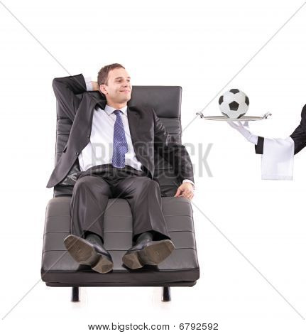 Young businessman relaxing on a sofa while the butler serving