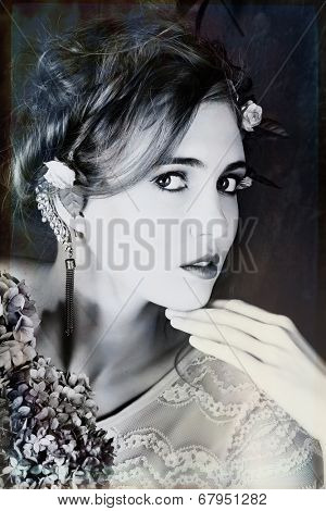 Romantic portrait of a beautiful woman with red hair and flowers in her hairstyle, wearing diamond ear cuff against grunge background