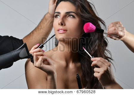 Beautiful young woman getting her hair and make up done
