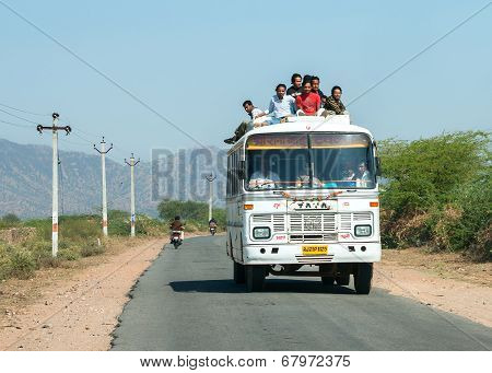Public Transport Bus Drives With Plenty Of Passengers On Roof.