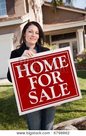 Hispanic Woman Holding Real Estate Sign In Front Of House