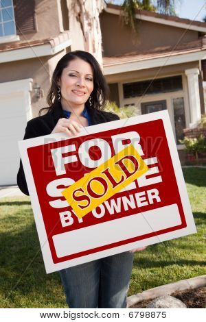 Hispanic Woman Holding Sold For Sale By Owner Real Estate Sign In Front Of House