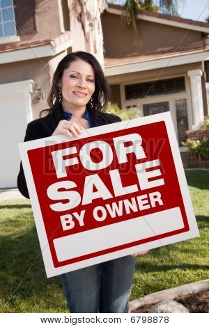 Hispanic Woman Holding For Sale By Owner Real Estate Sign In Front Of House