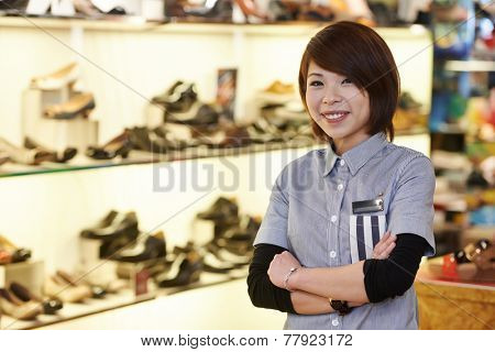 chinese young smiling female assistant seller in the shoe shop