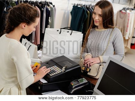 Happy woman customer paying with credit card in fashion showroom