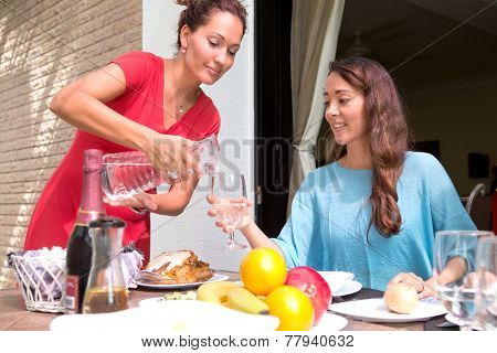 Two beautiful hispanic women enjoying an outdoor home meal together, one pouring water into a glass.