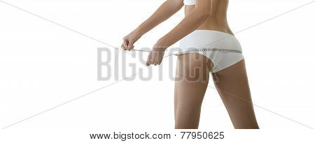Young beautiful woman measuring her torso with measuring tape