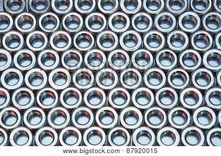 Shiny nuts on metal surface abstract industry background