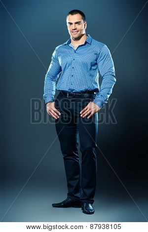 Full length portrait of a goodlooking man in a suit posing at studio.