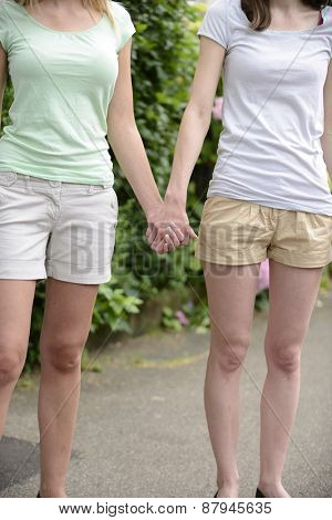 Lesbian couple holding hands outdoors