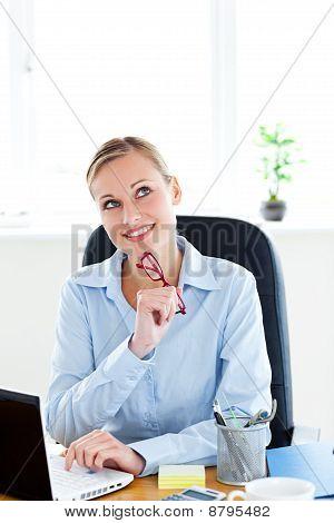Pensive Businesswoman Holding Glasses Sitting At Her Desk