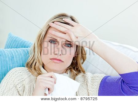 Diseased Woman Lying On A Sofa With Tissues And Feeling Her Temperature
