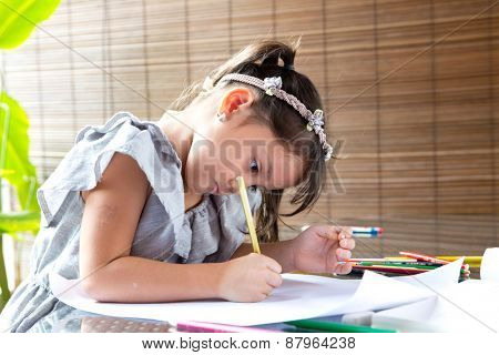 Young girl engross in coloring a drawing.