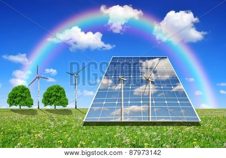 Solar energy panels and wind turbines on meadow. Green energy concept.
