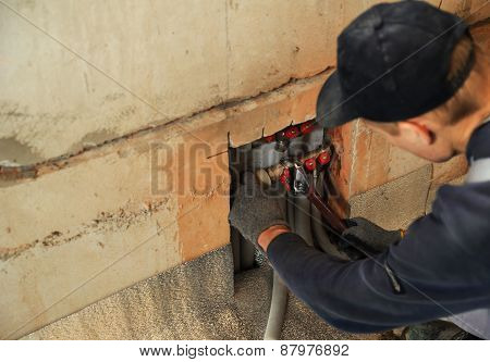 Man working installer connects the underfloor heating pipes poster