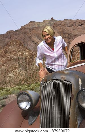 Mature Woman On Antique Car In The Desert
