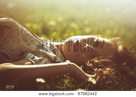 delicate beautiful young woman enjoy in sun lie in grass retro look and colors