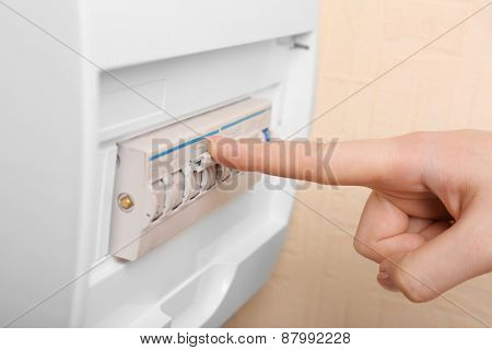 Woman turning off fuse box close up