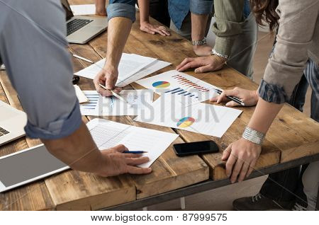 Businessman and woman discussing on stockmarket charts in office