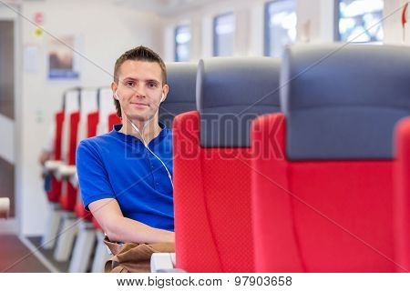Young happy man traveling by train