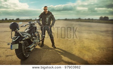 Biker in leather jacket standing by a motorcycle.