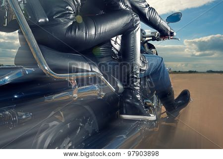 Biker Man and woman wearing black leather jackets riding on motorcycle