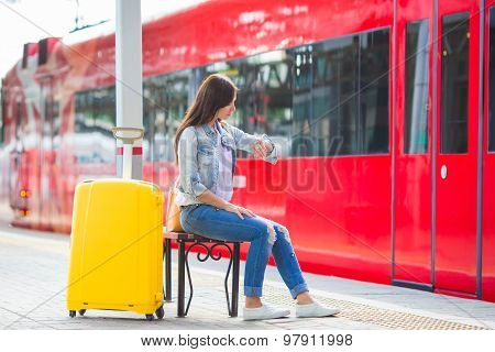 Young beautiful girl with baggage at a train station