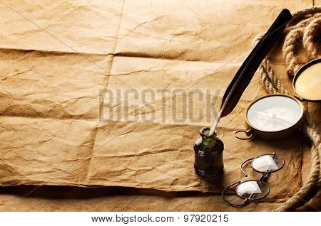 quill pen, inkwell, compass and rope on vintage paper background