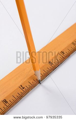 A pencil and ruler drawing a line on a white sheet of paper. Closeup in vertical format.