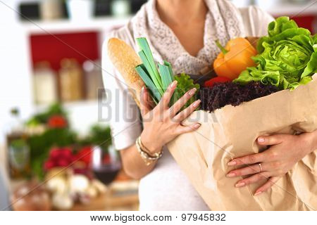 Young woman holding grocery shopping bag with vegetables Standing in the kitchen
