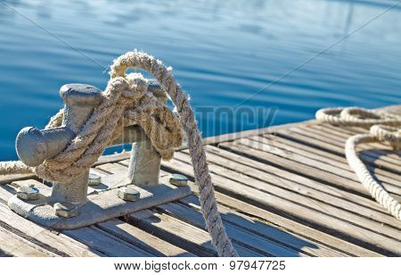 close up of rope tied up on a bitt on wooden dock. blue water in the background poster