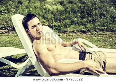 Shirtless Young Man Sunbathing in Lounge Chair. Filtered image