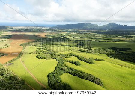 An aerial shot of the Kauai, Hawaii coastline showing green fields framed by shadows and blue sky.