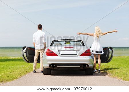 transport, travel, road trip and people concept - happy man and woman near cabriolet car at sea side poster